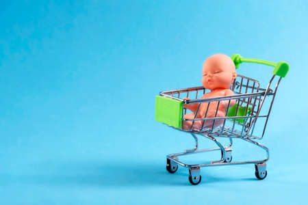 Doll sitting on a shopping cart on a blue background. Eco, surrogate motherhood, buy a child for money Stok Fotoğraf