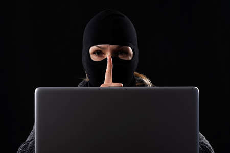 Cyber terrorist in a mask in a mask on a black background behind a laptop
