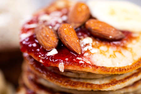 Stack of oat pancakes with jam and almonds in a wooden plate.