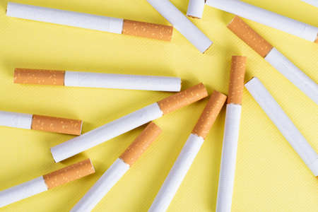 Lots of industrial cigarettes on a yellow background.