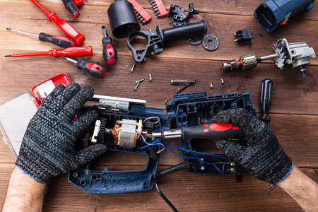 Power tool repair. Details of electrical appliance and repair tools on a wooden table in a repair shop.