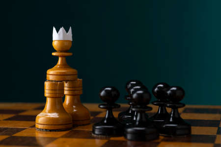 Little brave pawn wearing faux paper crown suit leading others to battle the enemy - business entrepreneur leadership concept.
