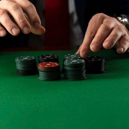 Businessman at green gaming table with casino chips. 免版税图像