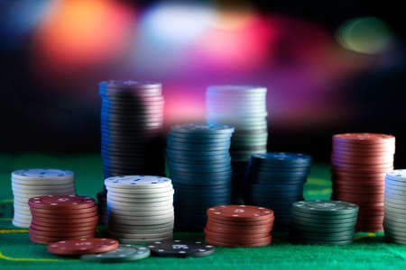 Blur background and chips, Stack of poker chips on a green table. Poker game theme.