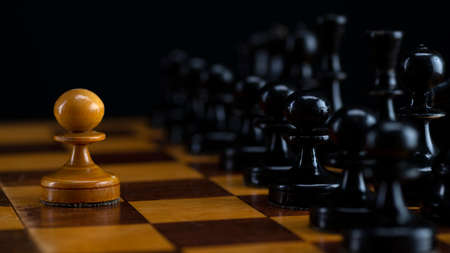 One white pawn against an army of black pieces on a chessboard.
