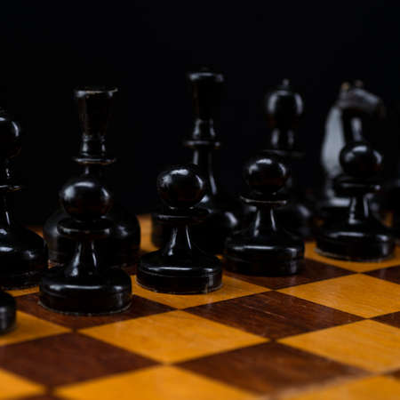 Black chess pieces on a chessboard. An army of black pawns on the table. 免版税图像