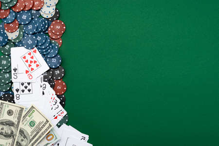 Cards and poker chips with american dollar bills on a green background. 免版税图像
