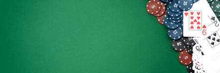 Cards and poker chips on a green background.