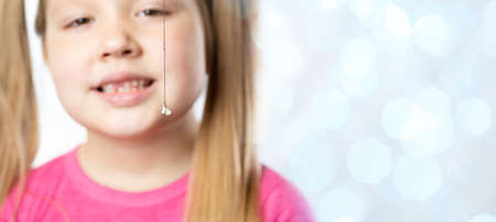 Little girl in pink holds a pulled out milk tooth on a thread.