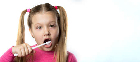 Preschool girl with first adult incisors and a toothbrush. The milk tooth has fallen out, and a permanent tooth grows in the open mouth. Dental hygiene concept. 免版税图像