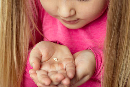 Little girl in pink holds a fallen milk tooth in her palms. Dental hygiene concept.