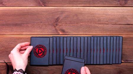 Minsk, Belarus, December 27, 2019. Fortuneteller's hands and divination cards on a wooden table. Divination concept, tarot cards, psychic.