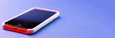 A modern smartphone lies on a blue surface or table in perspective with a place for text. 免版税图像