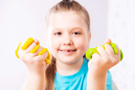 A fair-haired child without a milk tooth plays with purple mucus. Little beautiful caucasian girl is playing with many slugs and smiling. Play Slime Toy.