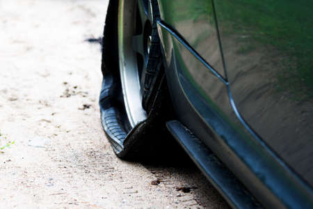 Punctured wheel of a modern car on the road. Car tire puncture Reklamní fotografie