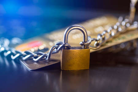 Credit card security, safe trading. Credit card closed with a padlock and chain.