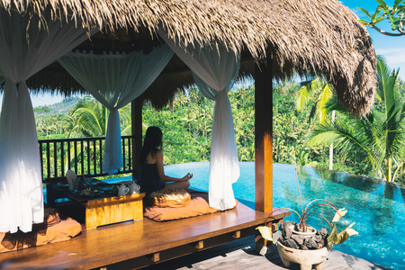 Girl meditating by the pool on a background of palms, Bali, Indonesia.The girl sits in a gazebo at a bali in a lotus pose and meditates with a view of the palms and the pool. Breakfast in Bali 스톡 콘텐츠