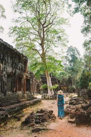 A tourist girl walks among the ancient temple buildings in Angkor, Cambodia.A young woman makes an exciting trip to the temple complex of Angkor.Scenic view of the ruins of ancient temples in Cambodia