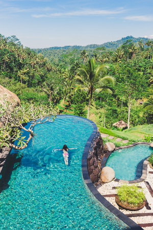 The girl is swimming in a large beautiful pool against the backdrop of lush tropical vegetation. A young woman swims in an outdoor pool with a beautiful view of palms, Bali, Indonesia. View from above.