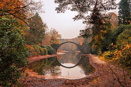 Rakotz Bridge (Rakotzbrucke, Devils Bridge) in Kromlau, Saxony, Germany. Colorful autumn, reflection of the bridge in the water create a full circle.Unusual and interesting places in Germany. 写真素材
