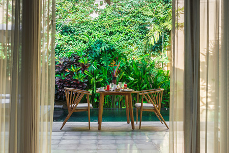 Schönes gemütliches Luxusfrühstück für zwei am privaten Pool, Bali, Indonesien. Ein Holztisch mit einem reichhaltigen gesunden Frühstück auf dem Hintergrund des Pools und tropischen Pflanzen.