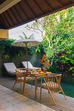 Beautiful cozy luxury breakfast for two at the private pool, Bali,Indonesia.A wooden table with an abundant healthy breakfast on the background of the pool and tropical plants.