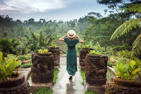 A young woman in a long dress of emerald color and wearing a hat is standing with her back against the background of a green tropical jungle, Ubud, Bali. Tourist girl in a romantic image in the midst of lush green trees Stok Fotoğraf