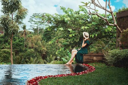 woman at a Private pool with rose petals in a luxury hotel in Bali Foto de archivo - 135490940
