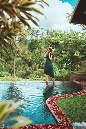 A young woman in a long dress of emerald color and wearing a hat walks over the side of an open private pool overlooking the tropical jungle, Ubud,Bali.Private pool with rose petals in a luxury hotel in Bali Foto de archivo - 135490943
