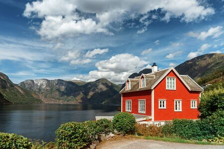 Typical Norwegian red house in the background of a picturesque fjord. Beautiful Norwegian landscape with a red house and atmospheric sky.