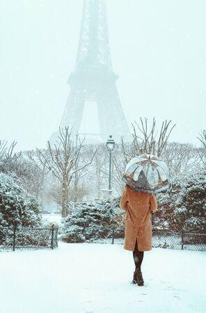 Une jeune femme vêtue d'un manteau beige marche sous un parapluie dans un Paris d'hiver enneigé sur fond de Tour Eiffel. Une fille brune romantique marche dans le fond des chutes de neige à Paris. Paris enneigé