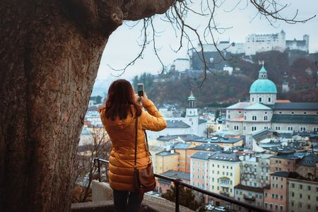 A young woman tourist photographs on a telephone a panorama of the medieval city of Salzburg.Very beautiful view of the winter Salzburg, the cathedral and the Hohensalzburg fortress, Austria