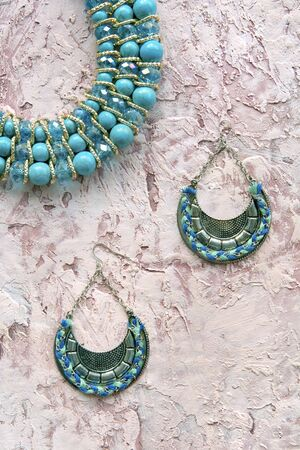 turquoise beads and earrings on a powdery textured background vertically in disfocus