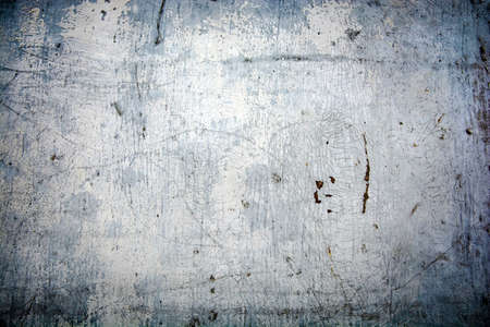 aged painted surface with cracked and peeled off gray-blue paint and rust with a dark vignette