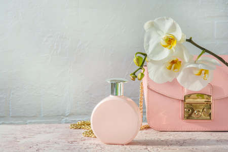 powdery perfume womens handbag and white orchid i on a light blurred brick wall background with empty space
