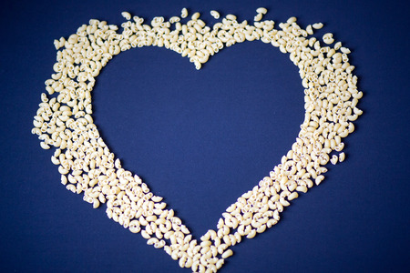 chaff: Heart of cereals and pasta on a blue background. Pasta and cereals.