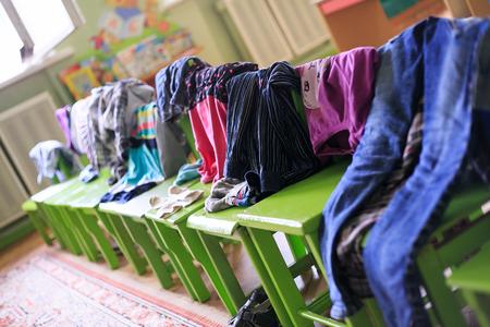 literas: La ropa de niños colgada en taburetes en el jardín de infantes en la hora de sueño. Foto de archivo