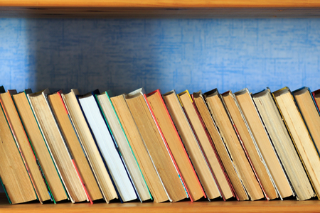 reverse: Books on the wooden shelf turned by a cover back Stock Photo