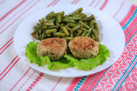 Cutlets with a stuffing with a garnish on a white plate on a light background