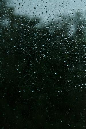 On transparent glass rain drops flow down Stock Photo