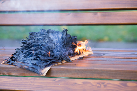 The burning book lies on a wooden bench. The book burns.