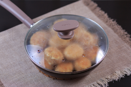 Fried cutlets on a frying pan on on a table on a gray background. Imagens