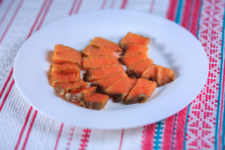 Red salty fish on a white plate on a bright background