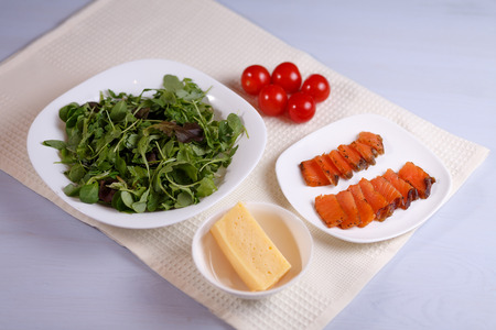 Greens, tomatoes, fish, cheese and sauce salad on a white plate on a white background.