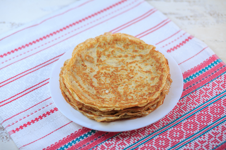 The Russian pancakes with a stuffing on a white plate on a light background. Maslenitsa. Stock Photo