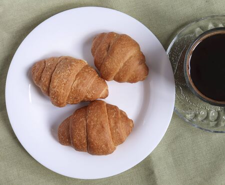Three fresh croissants on a white plate on a linen tablecloth and a cup of coffee. view from above.