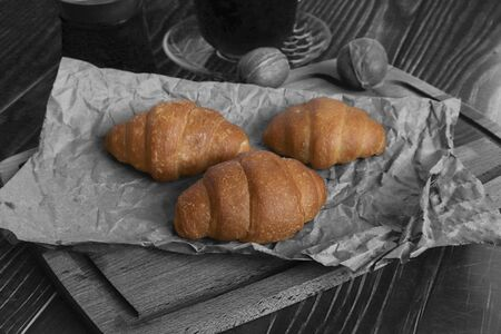 Fresh baked croissants on paper and wooden background. breakfast option, next to a turk and a cup of coffee. black and white aged background.