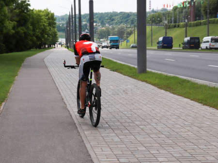 Mogilev. Belarus June. 15 2020 : A young fellow cyclist in a helmet and sports uniform ride a sports bike on a bike path in the city. view from the back. bike rental