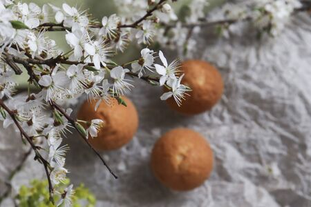 View from above. Selective focus on muffins through a bouquet of blossoming flowers. Breakfast in spring