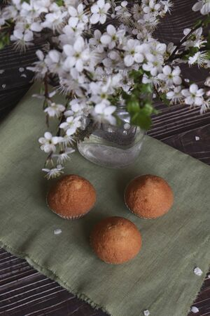 View from above. Cupcakes on paper and on a wooden brown background, vertical composition with white flowers.